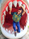 Women standing in jaws of shark Stock Images