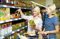 Women standing near shelves with canned goods Royalty Free Stock Photo