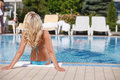 Women sunbathing rear view of blond hair women sunbathing on th woman the poolside Stock Photo