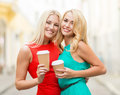 Women with takeaway coffee cups in the city holidays and tourism friends blonde girls concept beautiful Royalty Free Stock Photo