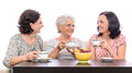 Women talking over coffee group of one senior and two adult ladies a cup of a bowl of fruits on black table indoor sitting on sofa Royalty Free Stock Images