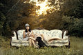 Women in twenties fashion on vintage couch blond and brunette posing a victorian outdoors with sunset and lots of greenery Royalty Free Stock Image