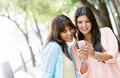 Women using a smart phone outdoors looking very happy Stock Images
