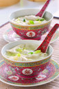 Won ton soup in pretty pink chinese bowls with spoons in vertical format Royalty Free Stock Photo