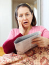 Wonder mature woman having grief after readed news in newspaper Royalty Free Stock Photography