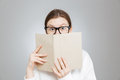 Wondered teenage girl in glasses covered face with book Royalty Free Stock Photo