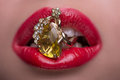 Wonderful blonde wearing jewelry woman with her red tempting lips holding fingering with topaz in her mouth Royalty Free Stock Image