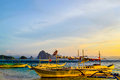 Wonderful view of the sunset sky shimmering sea cliffs on the horizon and the boats moored next to a sandy beach paradise resort Royalty Free Stock Photo