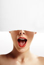 Wondering woman with partially closed face with a paper which close the of Royalty Free Stock Image