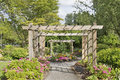 Wood arbor over garden path with plants trees and flowers blooming in summer Royalty Free Stock Photography