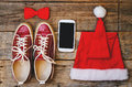 Wood background with phone sneakers red hood and a bow Royalty Free Stock Photo