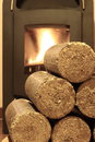 Wood briquettes for stoves background with fire Royalty Free Stock Photo