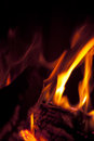Wood burning in fire closeup of with orange flames and dark background Royalty Free Stock Images