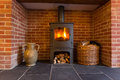 Wood burning stove in brick fireplace roaring fire inside with basket of cut ready for Stock Photos