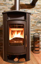 Wood burning stove in front of stonwall Stock Photography