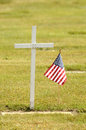 Wood cross a small american flag sits next to a simple on memorial day Stock Photos