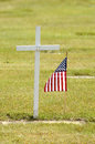 Wood cross a small american flag sits next to a simple on memorial day Royalty Free Stock Photos