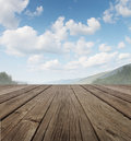 Wood deck as tranquil old rustic country patio floor perspective summer sky beautiful mountain range forest trees as symbol travel Stock Photography