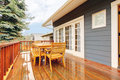 Wood deck with furniture and grey house. Royalty Free Stock Photo