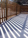 Wood fence shadow in snow Royalty Free Stock Photo