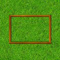 Wood frame on green grass field background Stock Photos