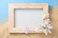 Wood frame and shell on sand and blue handicraft with coral texture background Stock Photos