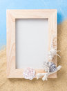 Wood frame and shell on sand and blue Royalty Free Stock Photo
