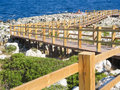 Wood gangway for the sea over rocks with people in platform on background Stock Images