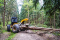 Wood hauling in the forest by a grapple skidder motion of machine and hauled logs blurred Royalty Free Stock Image