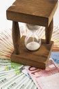 Wood hourglass closeup in a middle of euro banknotes circle Stock Photo