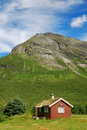 Wood house with green-roof under mountain. Stock Photos