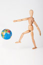 Wood mannequin kick a world globe disrespect in isolated on white Stock Photo