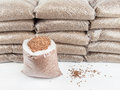 Wood pellets in bags an open bag of with a stack of bagged behind Royalty Free Stock Photography