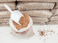 Wood pellets and scoop in an open bag of a stack of bagged behind Stock Photos