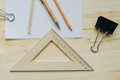 Wood pencil, pen, triangle, briefpapier clip on the desk in daylight. Office table