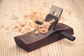 Wood planer and shavings closeup on wooden background Royalty Free Stock Image