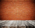 Wood plank tabletop, with defocus brick white wall texture background Royalty Free Stock Photo