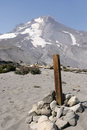 Wood post on mt hood a marking a hiking trail with the summit of in the background this area of is composed of loose volcanic Stock Images