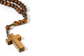Wood rosary with cross at left border and blank area right side white background Royalty Free Stock Image