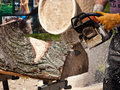 Wood sculptor using chainsaw a making a new piece of art a Royalty Free Stock Images