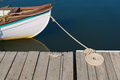 Wood skiff tied at dock with flemish coil bow of white wooden brown painted rail is to weathered wooden cleat spare line is Royalty Free Stock Photography