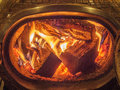 Wood stove with logs burning inside in fire on a cold winter night Stock Image