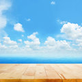 Wood table top on blue sea water and  bright summer sky background Royalty Free Stock Photo
