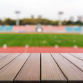 Wood table top on blur background of football field in stadium. Royalty Free Stock Photo