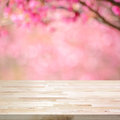 Wood table top on blurred background of pink cherry blossom flowers Royalty Free Stock Photo