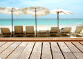 Wood table top on blurred blue sea and white sand beach background.