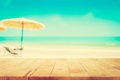 Wood table top on blurred blue sea and white sand beach background, vintage tone