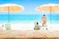 Wood table top on blurred white sand beach background