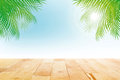 Wood table top on summer tropical sky background with green coconut leaves Royalty Free Stock Photo