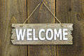 Wood welcome sign hanging on rustic wooden background Royalty Free Stock Photo